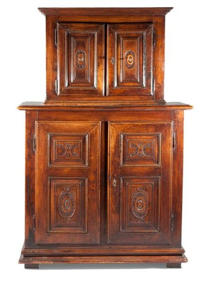 Petite armoire en deux corps, au corps supérieur en retrait, en noyer sculpté et...
