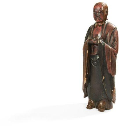 JAPON - XIXE SIÈCLE Statuette de moine debout en bois laqué brun et rouge, les mains...