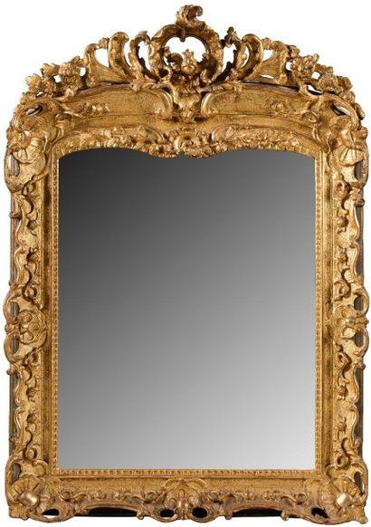 Miroir en bois redoré à décor ajouré et sculpté...