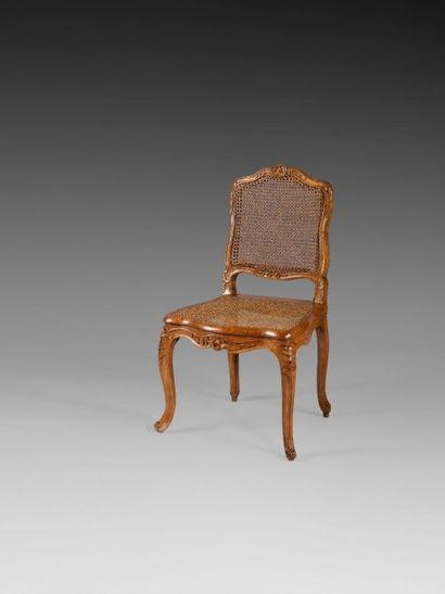 Chaise cannée en hêtre teinté, de forme mouvementée,...