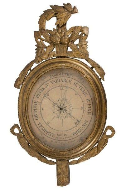 Baromètre circulaire en bois doré à décor de vases et feuillages stylisés; le cadran...