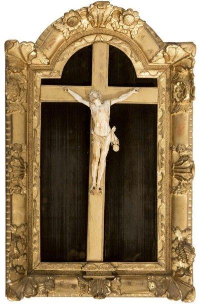 Crucifix en ivoire sculpté dans un cadre en bois redoré à décor de fleurs et feuillages....