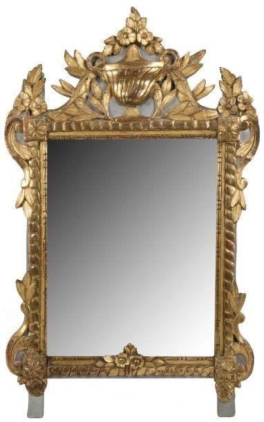 Miroir en bois peint et doré à décor de vase de fleurs, rosace et feuillages. Époque...