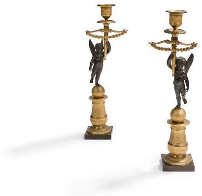 Paire de petits flambeaux en bronze patiné et doré, le socle en balustre à décor...
