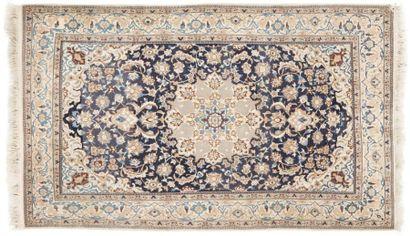 NAÏN Tapis à fond bleu à décor d'une rosace centrale et de rinceaux feuillagés, bordure...