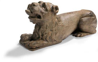 Lion en chêne sculpté en ronde bosse, couché, la tête relevée, gueule ouverte avec...