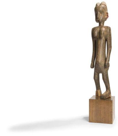 Une statue féminine scarifiée se tenant debout...