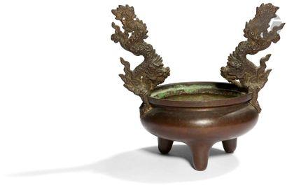 CHINE - XIXe siècle Brûle-parfum tripode en bronze à patine brune, les deux anses...