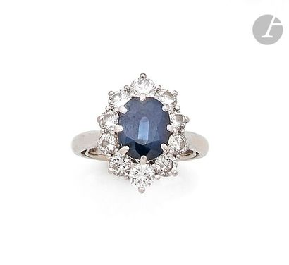 Bague en platine, ornée d'un saphir synthétique de forme ovale entouré de 10 diamants...