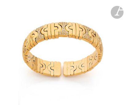 Bracelet torque orné de motifs en or jaune 18K (750) imbriqués, certains agrémentés...
