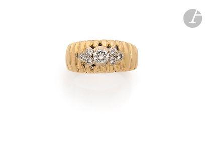 Bague godronnée en or 18K (750), ornée d'une fleur stylisée sertie de 7 diamants...