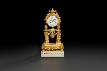 Petite pendule en bronze doré à deux colonnes...