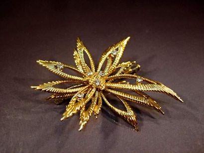 Broche en or stylisant une fleur sertie de...