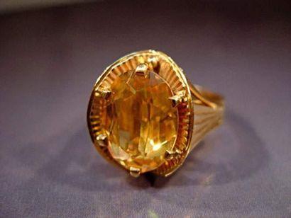 Bague en or sertie d'une pierre jaune ovale...