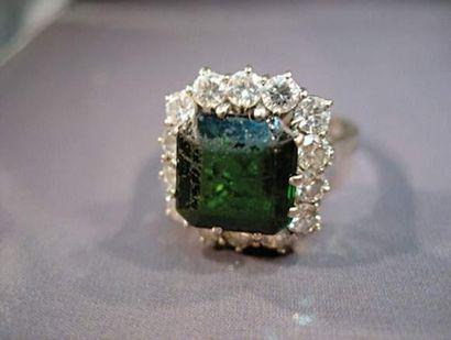 Bague en or gris centrée d'une pierre verte...