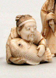 NETSUKE en ivoire représentant un homme assis...