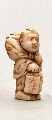 NETSUKE en ivoire représentant un homme debout...