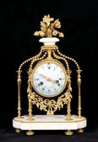 Pendule en marbre blanc et bronze doré. Le...
