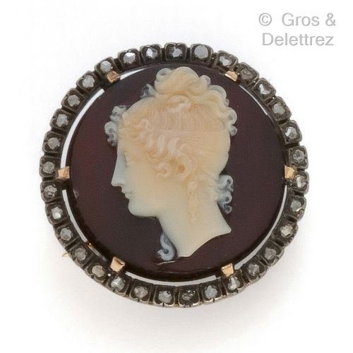 """A yellow gold and silver """"Circular"""" brooch, set with a cameo on carnelian in a f…"""