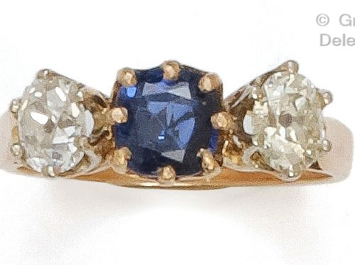 Yellow gold ring set with a cushion cut sapphire and two old cut diamonds. Finge…