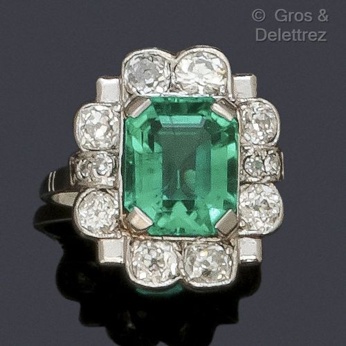 "A platinum ""Flower"" ring, set with a rectangular cut emerald in a circle of bril…"