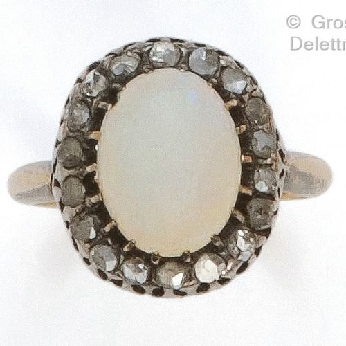 Yellow gold and silver ring, set with a cabochon opal in a circle of rose cut di…