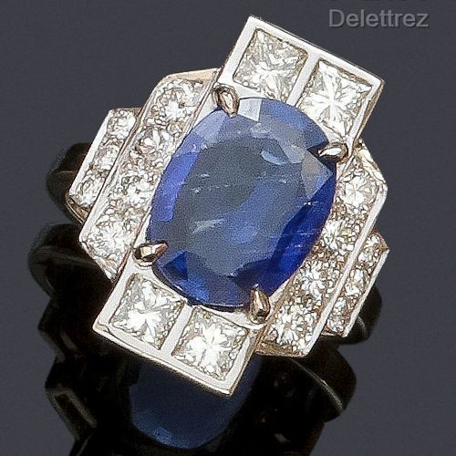 A white gold ring with geometric decoration, set with an oval sapphire and princ…