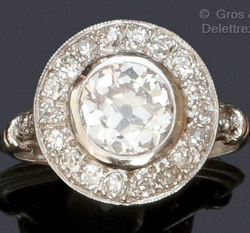 A white gold ring with a circular motif set with an old cut diamond in a setting…