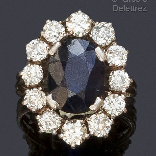 """White gold and platinum """"Flower"""" ring, set with an oval faceted sapphire in a br…"""