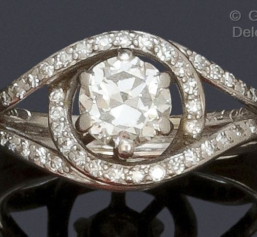 """MELLERIO A white gold """"Volutes"""" ring, set with a brilliant cut diamond in a sett…"""