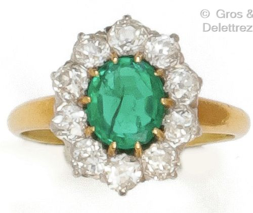 """Yellow gold and platinum """"Flower"""" ring, set with an oval emerald in a setting of…"""