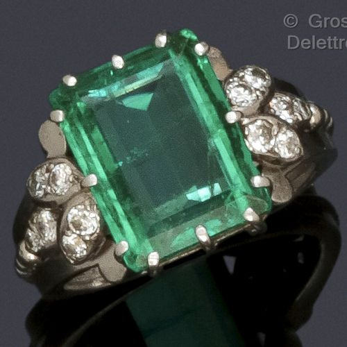 A platinum ring with pearl decoration, set with a rectangular emerald with step …