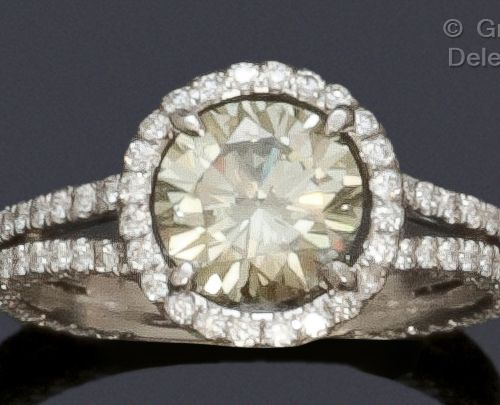 A white gold ring set with a brilliant cut diamond, surrounded by smaller diamon…