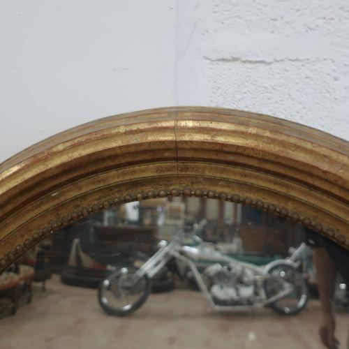 Grande glace ovale de style Louis XVI en bois stuqué doré à rangs de perles, 134…