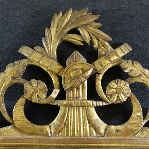 Glace à fronton de style Louis XVI en bois doré et sculpté de rinceaux, branches…