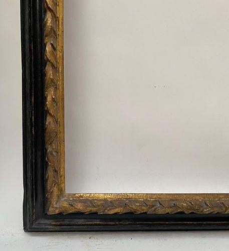 CADRE à profil renversé en bois noirci et doré, la feuillure à tors de lauriers.…