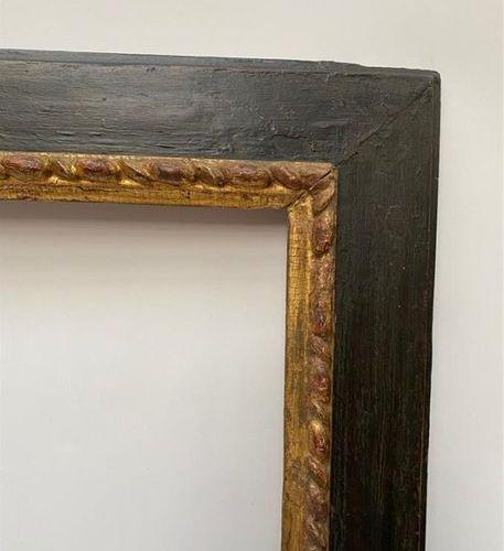 CADRE à profil renversé en bois noirci et feuillure dorée à godrons larmés. Ital…