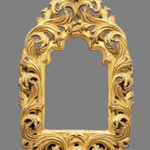 CADRE à fronton en bois sculpté et doré à décor de larges feuilles d'acanthe ajo…