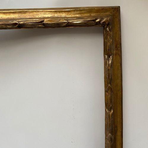 CADRE à profil renversé en bois mouluré, sculpté et doré à décor de tors de laur…