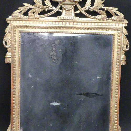 Glace en bois et plâtre doré à décor de filets de perles et couronne de laurier.…
