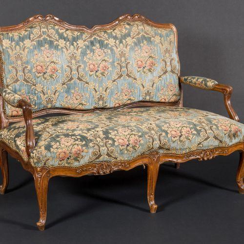 Canapé deux places en bois sculpté, à décor de rocailles et d'entrelacs.  Style …