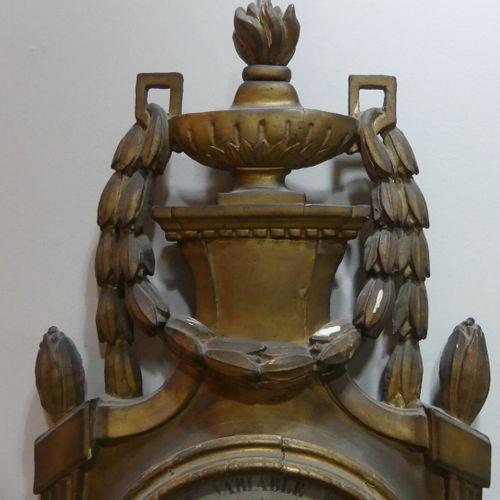 Baromètre en bois sculpté et doré surmonté d'un pot flammé et flanqué de guirlan…