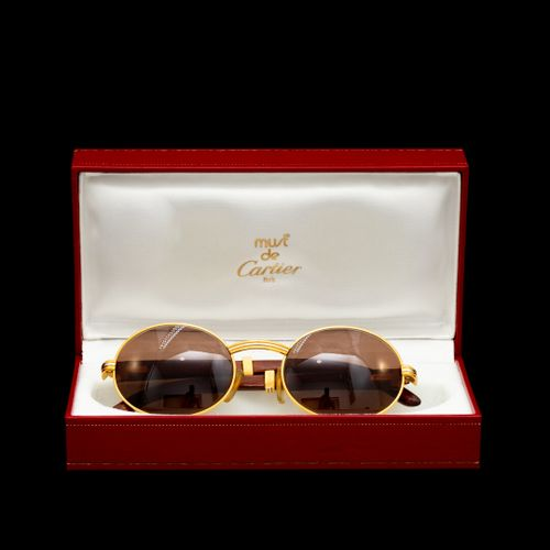 CARTIER  Paire de lunettes monture bois et métal doré. Verres correcteurs solair…