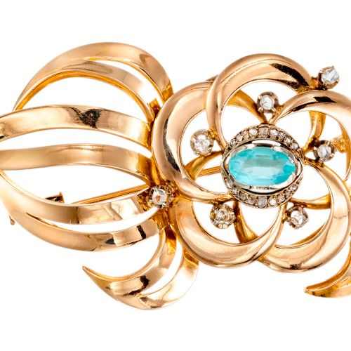 Broche Volute en or jaune sertie au centre d'une aigue marine ovale rehaussée de…