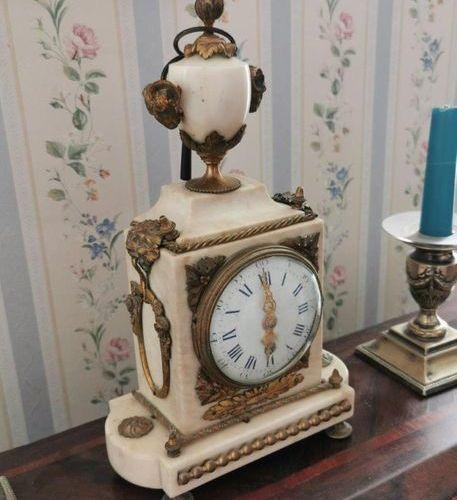 PENDULE BORNE en marbre blanc et bronze doré coiffé d'un vase de forme Médicis. …
