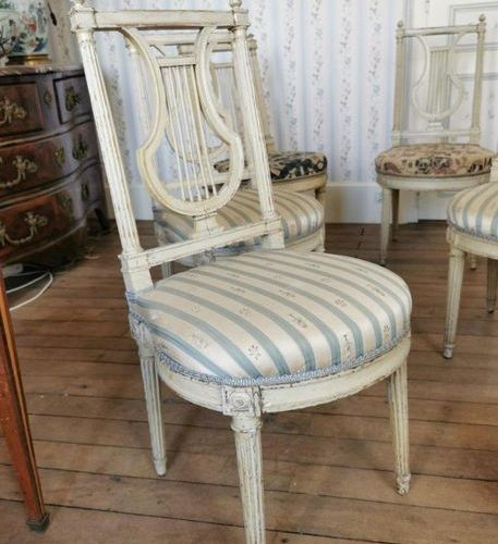 Five CHAIRS with LYRE backrest in moulded wood and white lacquered resting, the …
