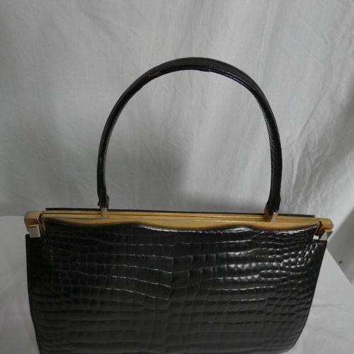 黑色质地的手提包,带金色搭扣。单把手。 尺寸:有把手时高39.5厘米,无把手时24厘米;长34厘米;最宽处8.5厘米。 磨损和污渍。按现状出售。 ,不允许看房。…