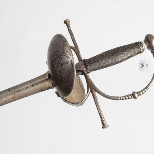Glockendegen, Taza 铃铛剑,塔扎  西班牙,17世纪下半叶。 铁制剑柄,有一个沼泽状的球状鞍座,护手上也有装饰。原本光滑的铃铛上的花纹雕刻在第…