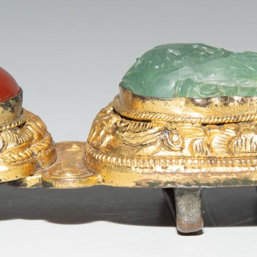 Gürtelschnalle 皮带扣  中国,清朝。绿色半透明的半宝石,可能是石英,形状为狮子和凸面红玉髓,镶嵌在镀金铜中。边缘有花卉浮雕装饰。长7厘米。