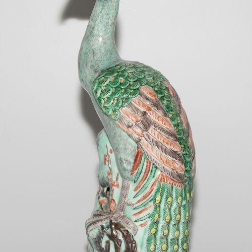 Pfauenfigur 孔雀雕像  中国,19/20世纪。 瓷器。雕刻的孔雀站在一棵梅花树上,采用Famille verte的颜色。高36厘米。